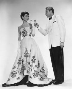 Hepburn in einem weißen Ballkleid mit schwarzem Blumenmuster, zusammen mit William Holden im Film