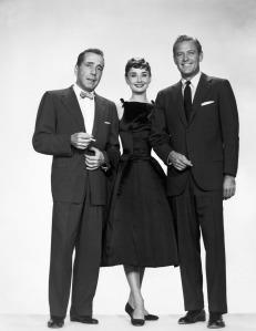 Hepburn im schwarzen Cocktailkleid mit Schleifen an den Schultern, zusammen mit den Leading Men Holden und Bogart im Film